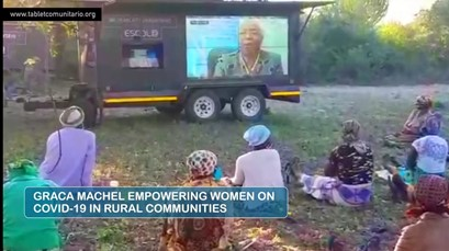 """A photo of women sitting on the ground outside looking at a screen. Title text reads """"Graca Machel Empowering Women on COVID-19 in Rural Communities"""""""