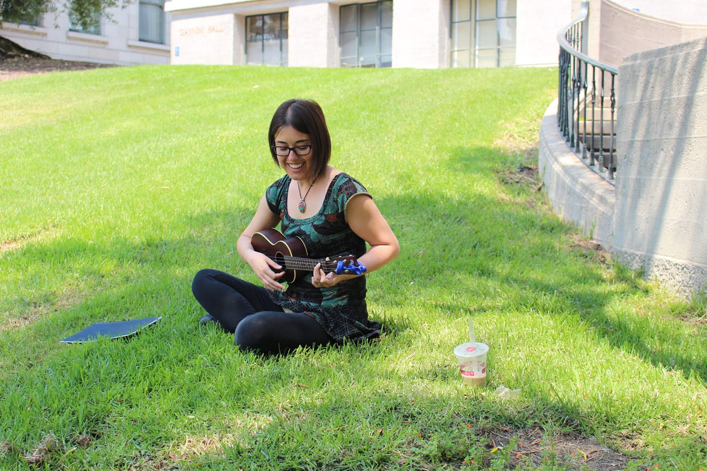 Cat Ming Hubbard sitting on the lawn in front of Giannini Hall with her ukulele.